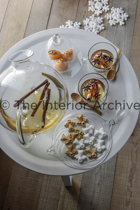 A warming winter tisane is served with Christmas delicacies on a table in the living room cabin