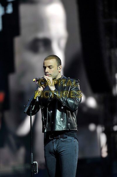 Chris Wolstenholme of Muse.Muse perform live in concert, Emirates Stadium, London, England, UK,.25th May 2013..music gig on stage performance performing half length playing harmonica microphone screen black leather jacket .CAP/MAR.© Martin Harris/Capital Pictures.