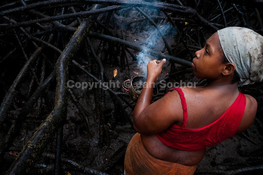 A Colombian girl carries a pot filled with a smouldering tropical wood while searching for shellfish in the mangrove swamps on the Pacific coast, Colombia, 12 June 2010. Deep in the impenetrable labyrinth of mangrove swamps on the Pacific seashore, hundreds of people struggle everyday, searching and gathering a tiny shellfish called 'piangua'. Wading through sticky mud among the mangrove tree roots, facing the clouds of mosquitos, they pick up mussels hidden deep in mud, no matter of unbearable tropical heat or strong rain. Although the shellfish pickers, mostly Afro-Colombians displaced by the Colombian armed conflict, take a high risk (malaria, poisonous bites,...), their salary is very low and keeps them living in extreme poverty.