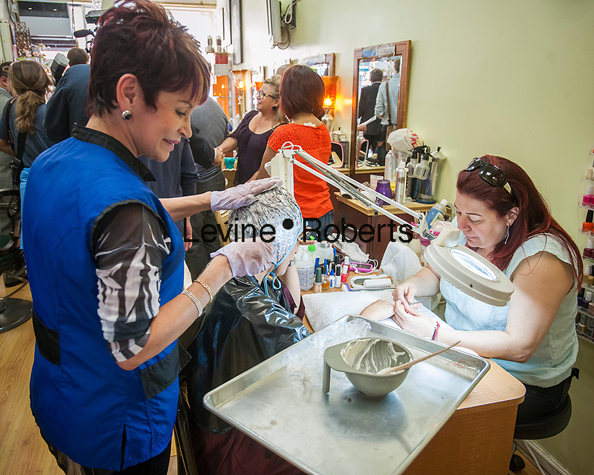 Customer has hair coloring and a manicure in an Hispanic owned beauty salon in the Jackson Heights neighborhood of Queens in New York on Friday, September 27, 2013.  Jackson Heights is a polyglot of ethnic groups ranging from Bangladeshis to South American to Indian to everyone else. (© Richard B. Levine)