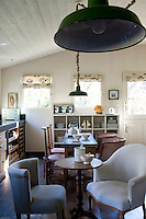 A pair of mismatched antique tables and chairs give the comfortably informal kitchen the air of an old-fashioned cafe