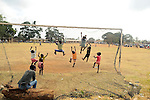 Young children in Likoni Kenya climbing on a soccer goal.
