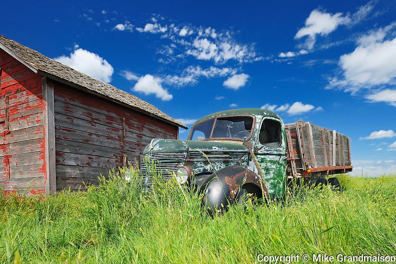 Old International truck and wodden grainery on farm<br /> Hazenmore<br /> Saskatchewan<br /> Canada