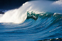 Large beautiful wave with dark cliff in the background.  Waimea shore break on the North Shore of Oahu, Hawaii.