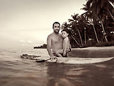 INDONESIA, Mentawai Islands, Kandui Resort, man standing in the water with his daughter and a surfboard (B&W)