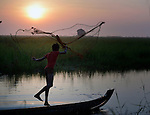 See Kim Lang, 15, throws a fishing net at dawn in the village of Phar Thruey in northern Cambodia.