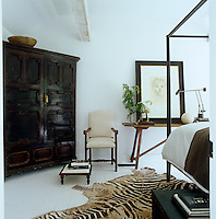 A large antique zebra-skin rug covers the floor of the guest bedroom where an antique cupboard serves as a wardrobe