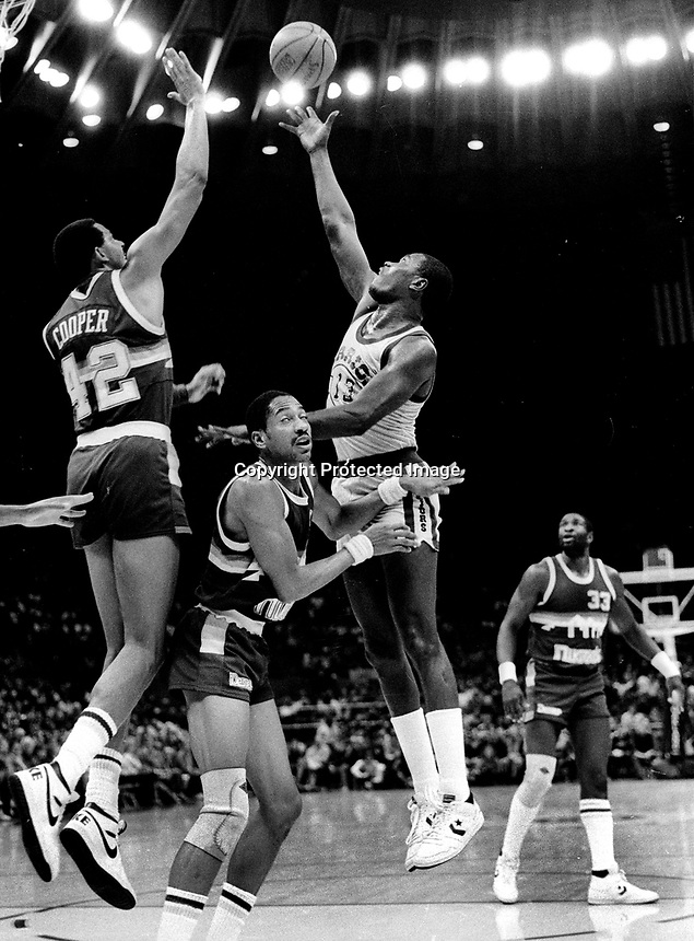 Golden State Warrior Larry Smith shoots over Denver Nuggets Wayne Cooper and Alex English. (1985 photo/Ron Riesterer)