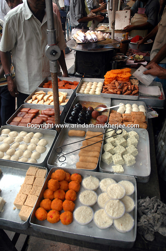 Bengali sweets selling on a foot path at Dalhousie Square in Kolkata. Street food stalls are serving the office goers for decades. All kind of Indian foods are available on the street at an affordable price. They sale them openly. Street food stalls are another results of unempoloyment and over poppulation. They serve millions of people in India. Kolkata, West Bengal,  India  7/18/2007.  Arindam Mukherjee/Landov