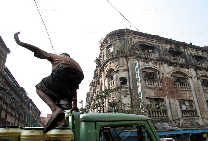 QS050114Calcutta030 20050114 CALCUTTA,INDIA:.A worker hops on to a loaded truck in Calcutta, India 14 January, 2005.