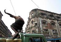 QS050114Calcutta030 20050114 CALCUTTA,INDIA:.A worker hops on to a loaded truck in Calcutta, India 14 January, 2005.