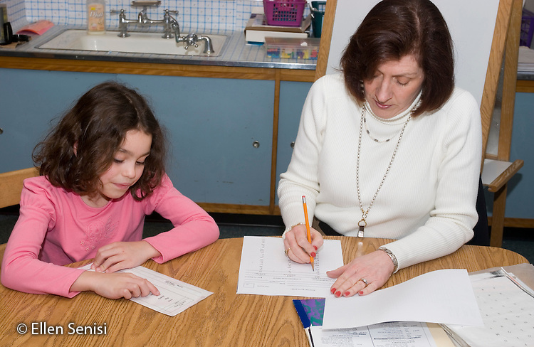 MR/Schenectady, New York.Zoller School- Inclusion classroom (urban, public, elementary school)/ Grade 1    reading teacher gives reading assessment test to student (Girl: 6, Puerto Rican-American-Caucasian)..MR:Spr1, Fit3.© Ellen B. Senisi