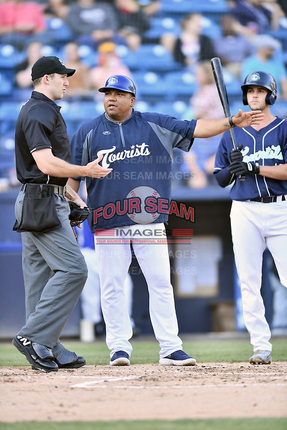 Asheville Tourists manager Robinson Cancel discusses a call with home plate umpire Jonathan Benken while Sean Bouchard (13) looks on during a game against the Greensboro Grasshoppers  at McCormick Field on May 10, 2018 in Asheville, North Carolina. The Tourists defeated the Grasshoppers 9-3. (Tony Farlow/Four Seam Images)