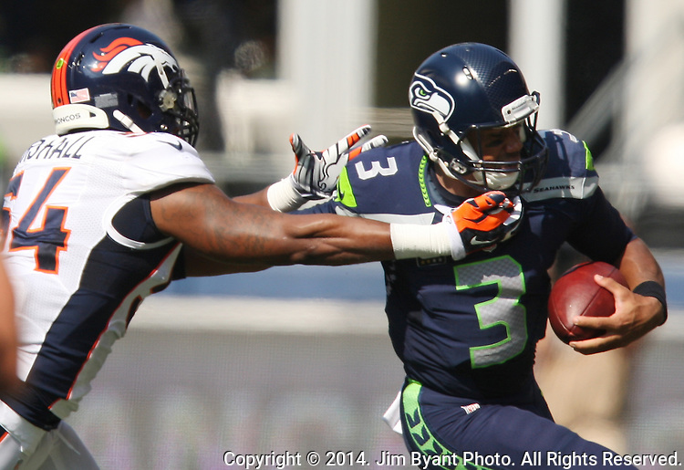 Seattle Seahawks quarterback Russell Wilson (3) scrambles away from Denver Broncos linebacker Brandon Marshall (54) ) at CenturyLink Field in Seattle, Washington on September 21, 2014.  Wilson completed 24 of 34 passes for 258 yards, two touchdowns and one interception in the 26-20 overtime win against the Broncos.  ©2014. Jim Bryant Photo. All rights Reserved.