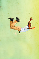 Antigua, St John, black schoolboy jumping and falling with green school wall in the background Few years ago photographers Anthony Asael and Stepahnie Rabemiafara dreamed a dream that seemed quite imposible: to visit every country of the World promoting arts and tolerance among children and, of course, taking photographs of them. With little money and resources but an impressing will, the duo got an astonishing goal. In four years they visited 300 schools in 192 countries where kids participating of the project created 18,000 pieces of artwork. <br />