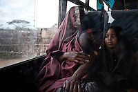 A Somali refugee woman and her children on a bus provided by UNHCR and IOM to move a group of stranded vulnerable refugees from Hamey, Kenya near the Somalia border refugee camps near Dadaab, Kenya. Most refugees make the journey from the border to the camps by foot at great peril. The roads are lined with bandits and many women report  being raped during the trek.