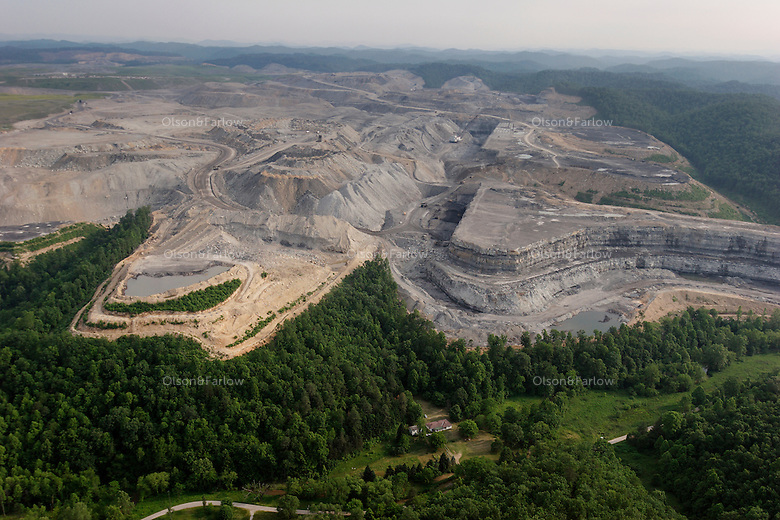 Mining companies can legally come within 100 feet of a family cemetery and 300 feet from a home. The Hobet 21 coal mine owned by Arch Coal looms over one of the few remaining homes in Mud, W.V.<br /> <br /> In 2003, Hobet 21 produced about 5.2 million tons of coal, making it among the largest surface mines in the state. The Lincoln County mine has been expanding over hills and valleys, filling in Connelly Branch creek.   <br /> <br /> The town of Mud hasn't been much of a community in the couple of decades since the post office closed, but in 1998 around 60 residents remained.  They had two churches and a ball field. In early 1997, Big John, the mine's 20-story dragline, moved above Mud and more houses, near this one, were bought and destroyed.