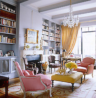 This library-cum-living room is furnished with an elegant pair of pink-upholstered bergere chairs and an ottoman used as a coffee table on an antique Aubusson rug