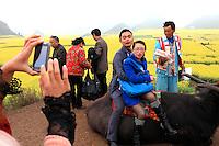 Luoping, Yunnan. Le village de Jinji Lin. Photo souvenir d'un couple à l'aide d'un smart phone. Un flot de touristes massif assaille les collines de Jinji Lin pour partager en famille quelques jours de congé.///Luoping, Yunnan. The village of Jinji Lin. Photo souvenir by a couple using a smart phone. A massive stream of tourists assails the hills of Jinji Lin to share with their familes a few days off.