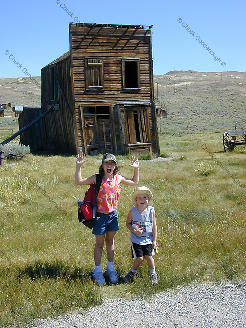 """Tourist Children act out a Ghost Town """"holdup"""" in the Mining Town of Bodie in the Eastern Sierra's of California."""