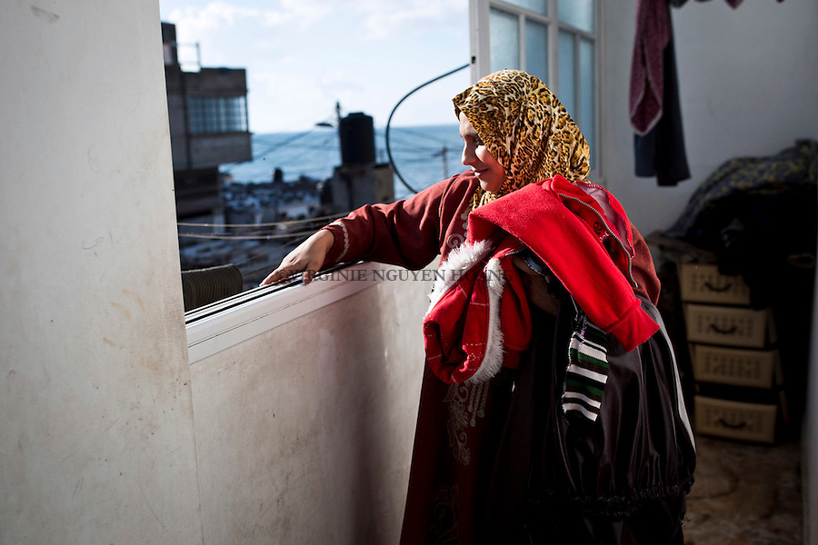Gaza, Beach Camp: ... is doing her laundry. From her window, she can see the mediterranian sea where here husband fish every nights. <br /> <br /> Gaza, Beach camp: .... pend le linge. De sa fen&ecirc;trr elle peut apercevoir la mer m&eacute;dit&eacute;ran&eacute;e o&ugrave; son mari p&ecirc;che toutes les nuits.