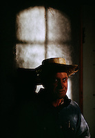 Stark light from a window falls on the straw hat and face of a monk at Shasta Abbey, a Zen Buddist Monastery near Mount Shasta. It was founded in 1970 as a training place for monks.