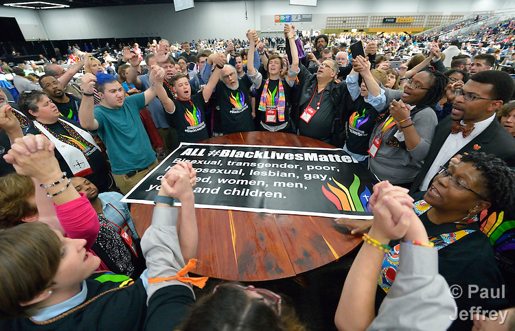 Members of the Black Lives Matter movement disrupt the May 16 proceedings of the 2016 United Methodist General Conference in Portland, Ore. The demonstrators marched into the plenary session chanting slogans and here hold a meeting around the central communion table. Photo by Paul Jeffrey.