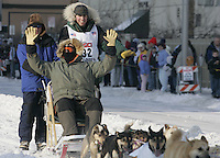 Matt Hayashida leaves the Anchorage start line on 4th avenue during the start of the Iditarod as his Iditarider waves to the crowd.