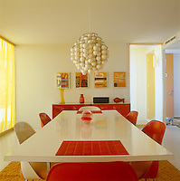 The dining room has a red and white colour scheme and chairs by Eero Saarinen and a pendant light by Verner Panton