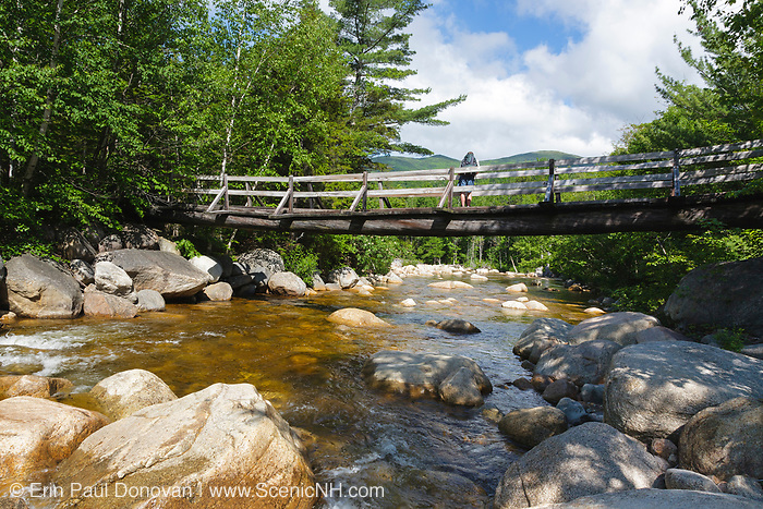 A hiker on foot bridge along the Thoreau Falls Trail in the Pemigewasset Wilderness of New Hampshire. This bridge crosses the East Branch of the Pemigewasset River.