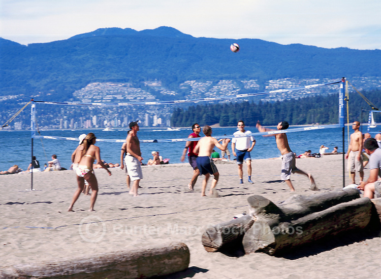 People playing Beach Volleyball at Kitsilano Beach along English Bay, Vancouver, BC, British Columbia, Canada, Summer - West Vancouver, Stanley Park, and North Shore Mountains (Coast Mountains) beyond