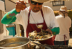 """Miguel Romero, of """"Aroma Concepcion,"""" of San Jose, prepares Washington oysters at the 29th annual Pittsburg Seafood and Music Festival on Sunday September 8th, 2013 in Pittsburg, California.  Photo/Victoria Sheridan"""