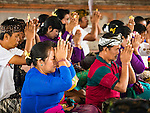16 JULY 2016 - UBUD, BALI, INDONESIA: People pray during the prayer service before the mass cremation in Ubud Saturday. Local people in Ubud exhumed the remains of family members and burned their remains in a mass cremation ceremony Wednesday. Almost 100 people were cremated and laid to rest in the largest mass cremation in Bali in years this week. Most of the people on Bali are Hindus. Traditional cremations in Bali are very expensive, so communities usually hold one mass cremation approximately every five years. The cremation in Ubud concluded Saturday, with a large community ceremony.     PHOTO BY JACK KURTZ