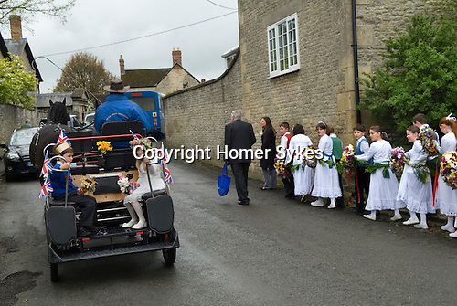 Charlton-on-Otmoor Oxfordshire Ist of May Day Celebrations. Children from the Church of England St Mary the Virgin Primary School process to the village church to have their May garlands blessed. They sing the traditional May Day song twice on route and once outside of the church.2014.