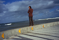 PUNTA DEL ESTE, URUGUAY  - MARCH 2005:  A young man watches surfers in Punta del Este, Uruguay.  (photo by Landon Nordeman)