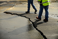 Napa Public Works employees inspect a buckled section of pavement that ruptured a water main in a residential neighborhood after a magnitude 6.0 earthquake struck in the early morning of August 24, 2014, in Napa, California.