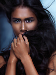 Expressive emotional beauty portrait of a young woman covering her face with her long hair in dramatic light