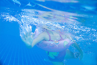Little girl with inflatable ring underwater in a swimming pool, Cuba