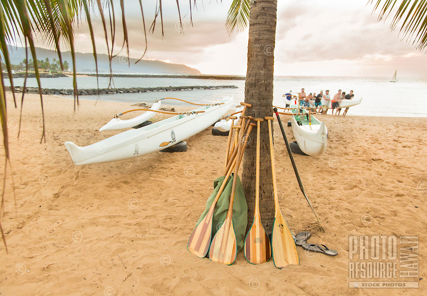 A team of paddlers carry an outrigger canoe up the beach, Hale'iwa Beach Park, O'ahu.
