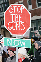 "People take part in the March For Our Lives protest, walking from Roxbury Crossing to Boston Common, in Boston, Massachusetts, USA, on Sat., March 24, 2018, in response to recent school gun violence. Here, a person holds a hand-made sign that looks like a stop sign and reads on one side, ""Stop the Madness / End Gun Violence,"" and on the other, ""Stop the Guns / Now."""