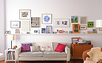 Photographs, paintings and other ornaments are displayed on a narrow shelf across the living room wall