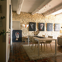 A living/dining room with a beamed ceiling, exposed stone wall and tiled floor. The room is furnished with retro style furniture and contemporary paintings hang on the wall.