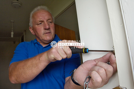 Housing Association tradesman fitting a chain guard to front door UK