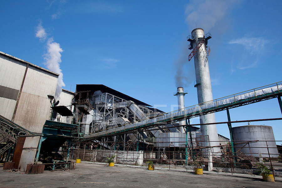 Smoke stacks and holding tanks outdoors at the URSUMCO (Universal Robina Sugar Milling Corporation) cane sugar mill near Bias City on Negros Island, Philippines.