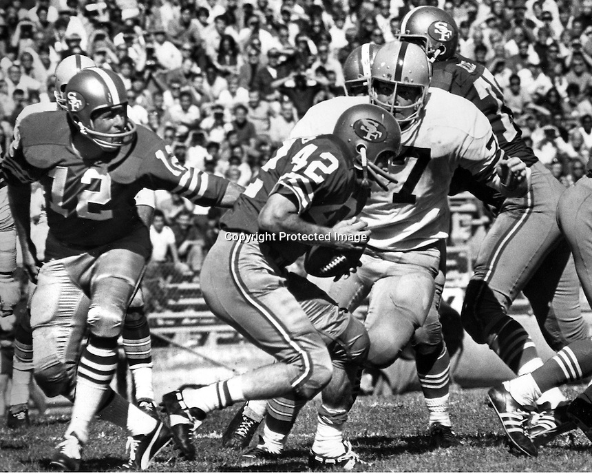 San Francisco 49er quarterback John Brodie hands off to Doug Cunningham #42, Green Bay Packers lineman #77. (Sept 20,1970 photo/Ron Riesterer)