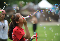 NWA Democrat-Gazette/ANDY SHUPE<br /> Daisy Mota, an incoming freshman at the University of Arkansas from Dallas, concentrates Saturday, June 17, 2017, while blowing soap bubbles during the Juneteenth celebration in The Gardens on the University of Arkansas campus in Fayetteville. Juneteenth marks the anniversary of the emancipation of slaves in the United States.