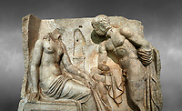 Close up of a Roman Sebasteion relief  sculpture of Io and Argos Aphrodisias Museum, Aphrodisias, Turkey.  Against a grey background.<br /> <br /> A powerful hero is folding a sword gazing closely at a half naked and dishevelled young heroine who sits on a chest like stool. Between, on a pillar base stood a small, separately added statue of a goddess ( now missing). The scene follows a scheme used in the relief panels &ldquo;Io guarded by Argos&rdquo;. Io was one of Zeus&rsquo;s lovers, and Argos was a watchful giant sent to guard her by Hera, Zeus&rsquo;s wife.
