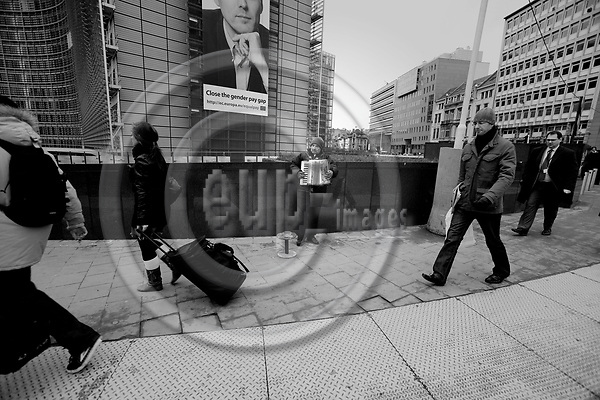 BRUSSELS - BELGIUM - 20 FEBRUARY 2008 -- A poor musician playing harmonica next to EC Headquarters at Round Point Schuman hoping that people will leave him some money. The banner on the EU building is a campaign for equal gender pay for equal work.  Photo: Erik Luntang/EUP-IMAGES/