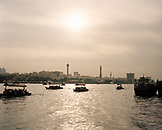 UNITED ARAB EMIRATES, Dubai, Dubai Creek, people traveling on water taxis with a minaret and mosque in the background