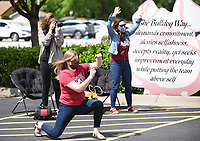 Teachers and friends cheer on passing graduating seniors Monday, May 18, 2020, during the Springdale High School Bulldog Bash at the High School. Seniors were given the opportunity to drop off school materials, pick up signs and receive cords and awards. The event kicked off the 12 Days of Graduation event. Check out nwaonline.com/200519Daily/ and nwadg.com/photos for a photo gallery.<br /> (NWA Democrat-Gazette/David Gottschalk)